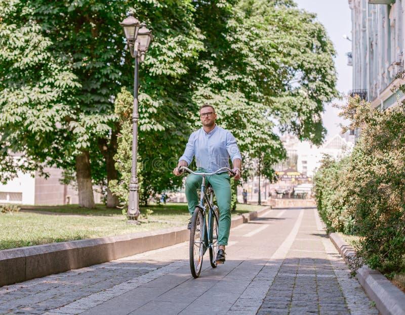 Bicicleta del montar a caballo del hombre de negocios a trabajar en la calle urbana por mañana fotografía de archivo