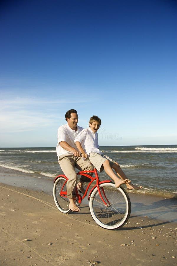 Bicicleta del montar a caballo del papá y del hijo imagen de archivo