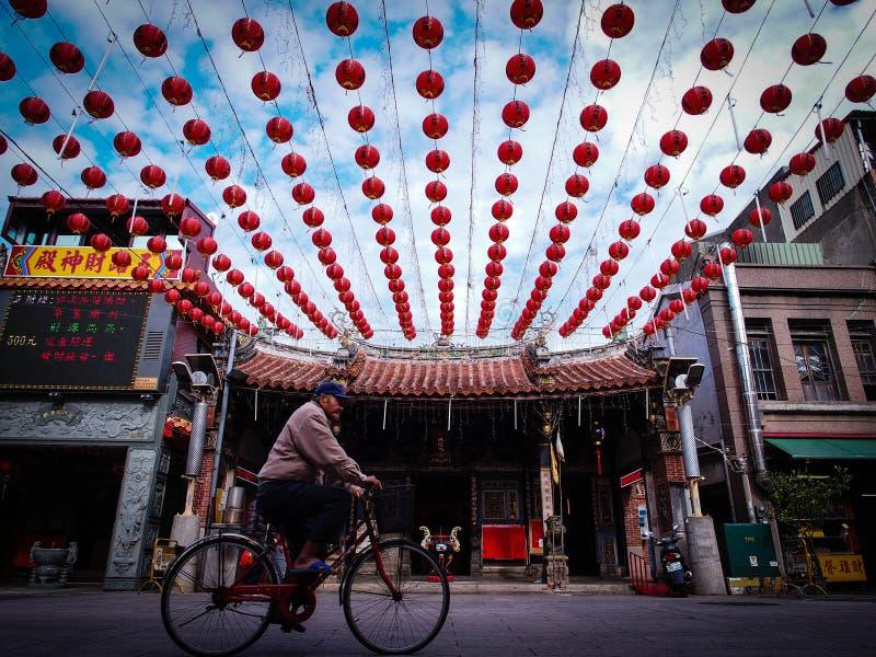 Bicicleta del montar a caballo del viejo hombre delante de un templo de Asia imagen de archivo libre de regalías