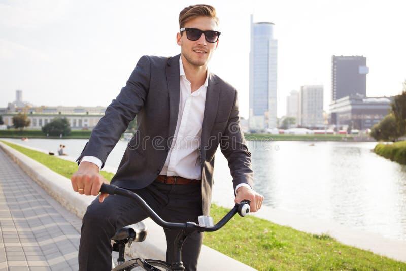 Bicicleta del montar a caballo del hombre de negocios a trabajar en la calle urbana por mañana imagen de archivo libre de regalías
