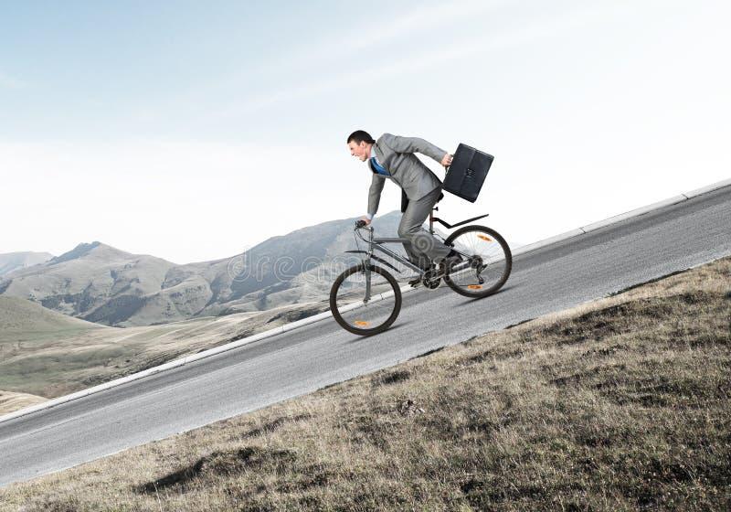 Bicicleta del montar a caballo del hombre joven en la carretera imagen de archivo libre de regalías