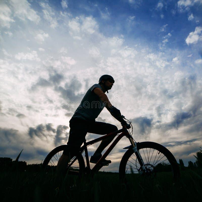 Bicicleta del montar a caballo del hombre sobre fondo del cielo de la puesta del sol imagenes de archivo