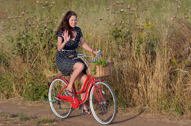 Bicicleta del vintage del montar a caballo de la mujer joven fotos de archivo libres de regalías