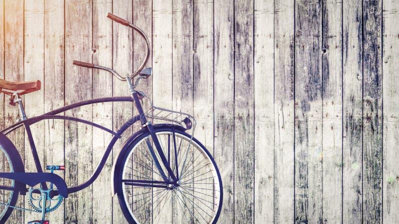 Bicicleta del vintage parqueada al lado de la pared de madera stock de ilustración