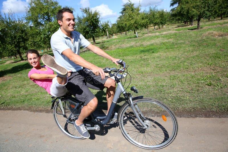 Bicicleta divertida del montar a caballo de los pares el día soleado fotos de archivo