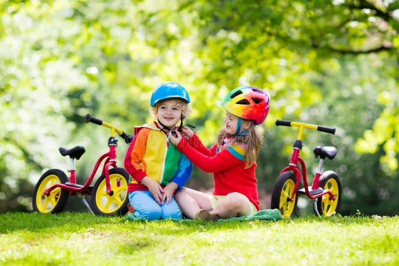 Bicicleta do equilíbrio do passeio das crianças no parque imagem de stock