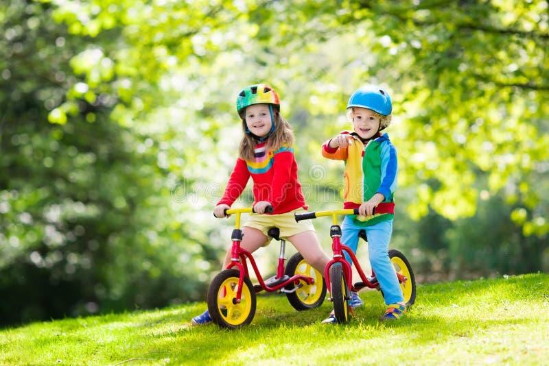 Bicicleta do equilíbrio do passeio das crianças no parque imagem de stock royalty free