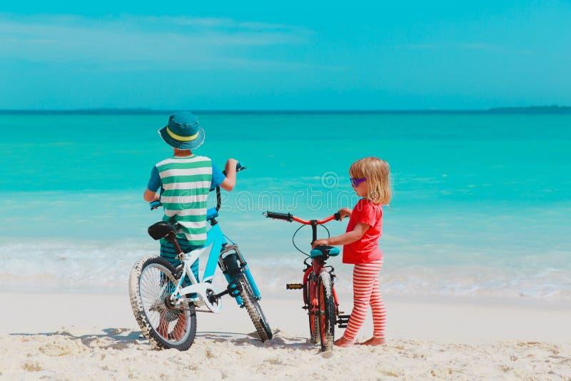 Bicicleta do passeio do rapaz pequeno e da menina na praia imagem de stock royalty free