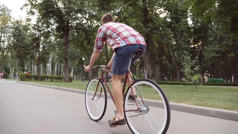 Bicicleta do vintage da equitação do homem novo na aleia do parque Ciclagem desportiva do indivíduo exterior Estilo de vida ativo fotografia de stock royalty free