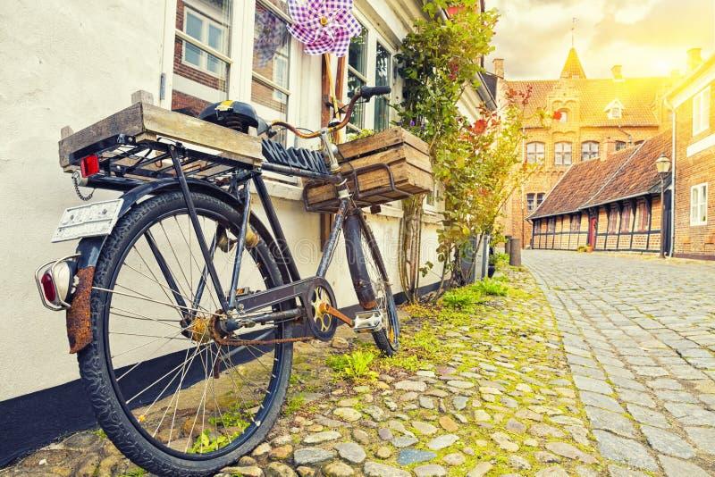 Bicicleta do vintage na parede no por do sol, rua velha da casa da cidade, imagens de stock royalty free