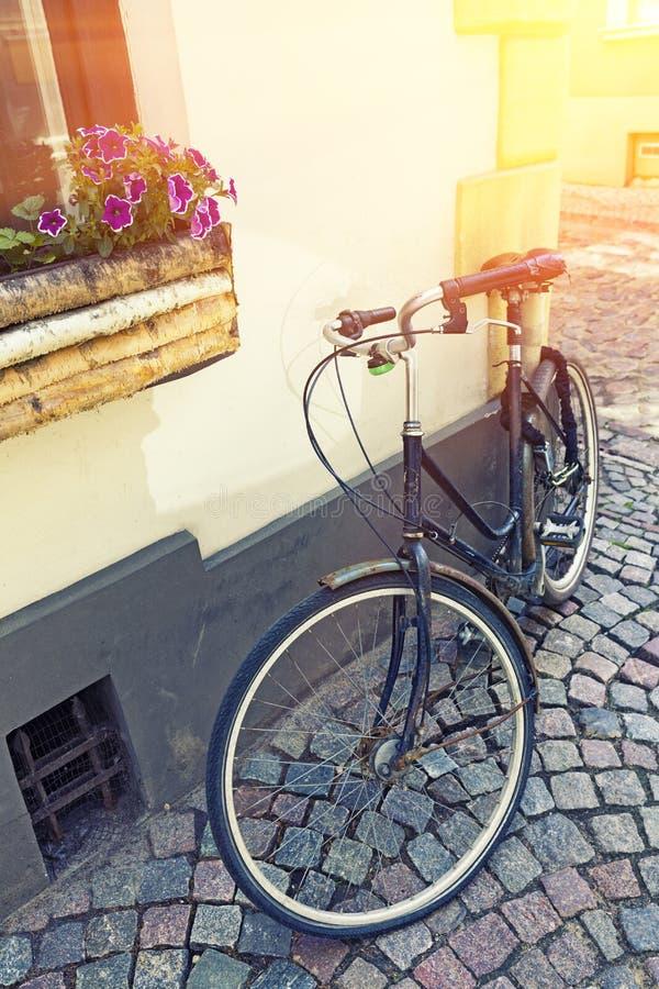 Bicicleta do vintage na parede no por do sol, rua velha da casa da cidade, fotos de stock royalty free