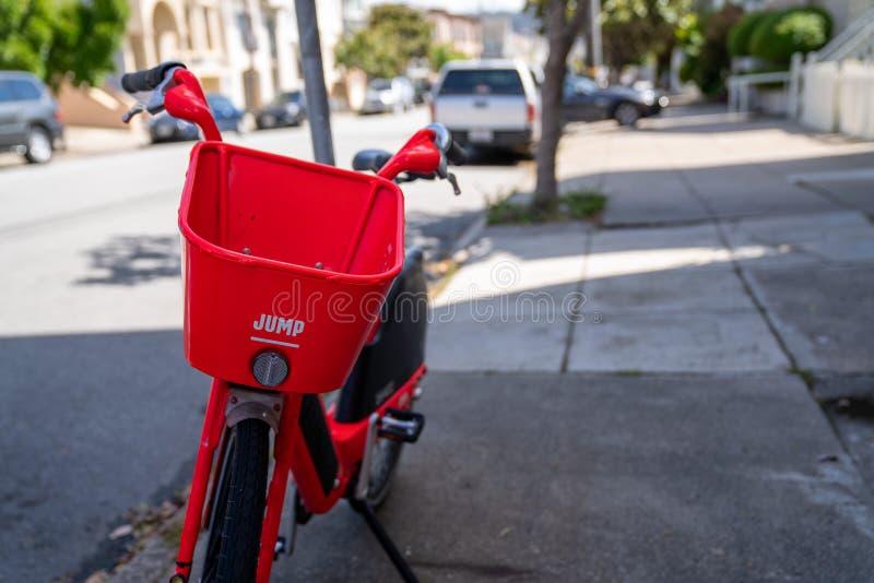 Bicicleta eléctrica a pedido del SALTO rojo, compañía poseída por Uber, parqueado en la calle residencial foto de archivo