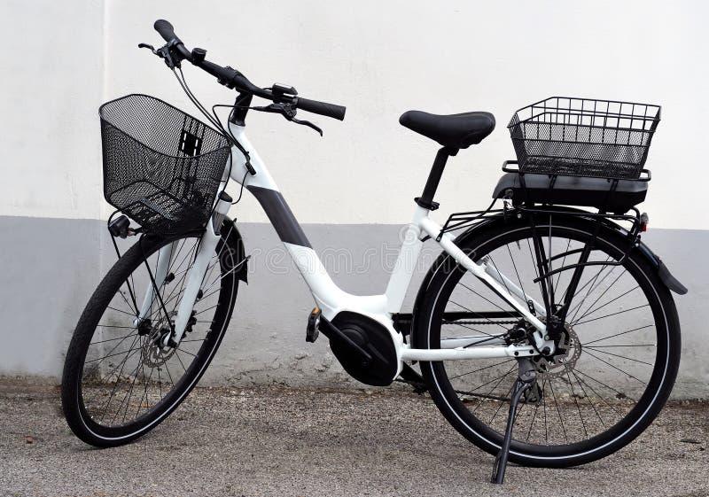 Bicicleta elétrica brandnew, ou bicicleta de e, para mulheres A bateria nova deve finamente bastante ser colocada sob a cesta tra fotos de stock