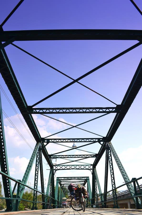 Bicicleta en el cielo histórico del puente del hierro, nublado y azul