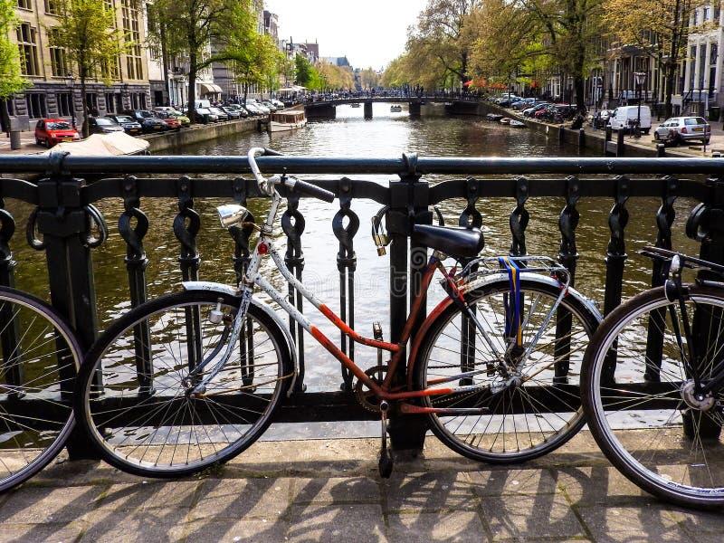 Bicicleta en un canal en Amsterdam fotos de archivo