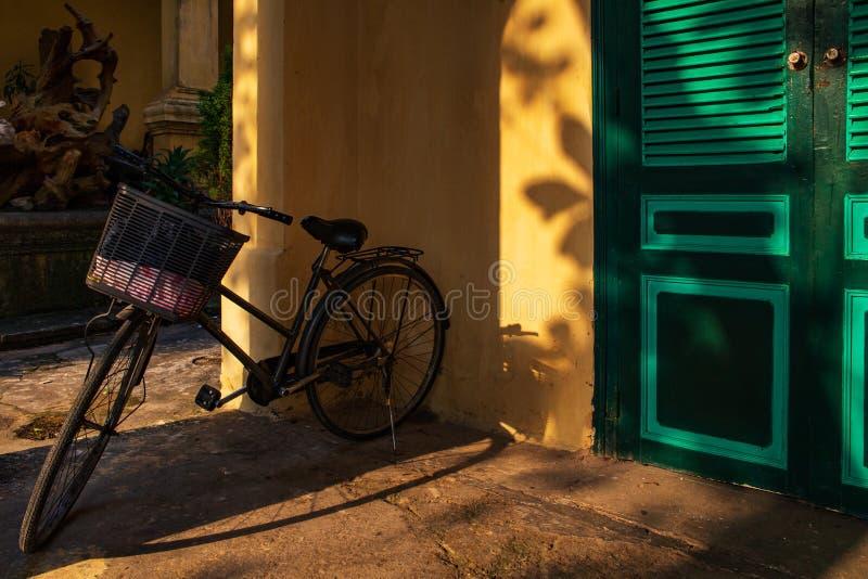 Bicicleta en un mirador por una pared amarilla con las puertas verdes con los rayos de luz del sol Tiro en la ciudadela larga de  imagen de archivo