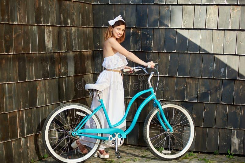 Bicicleta feliz bonita da equitação da mulher na cidade fotografia de stock