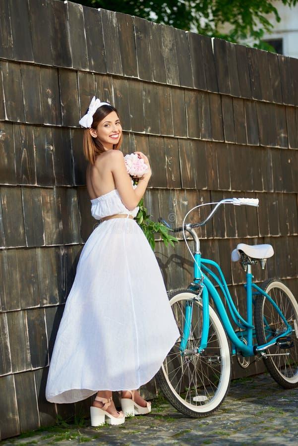 Bicicleta feliz bonita da equitação da mulher na cidade fotos de stock royalty free