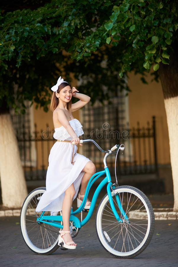 Bicicleta feliz bonita da equitação da mulher na cidade fotos de stock