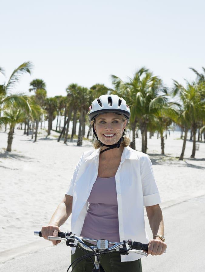 Bicicleta feliz da equitação da mulher na praia imagens de stock