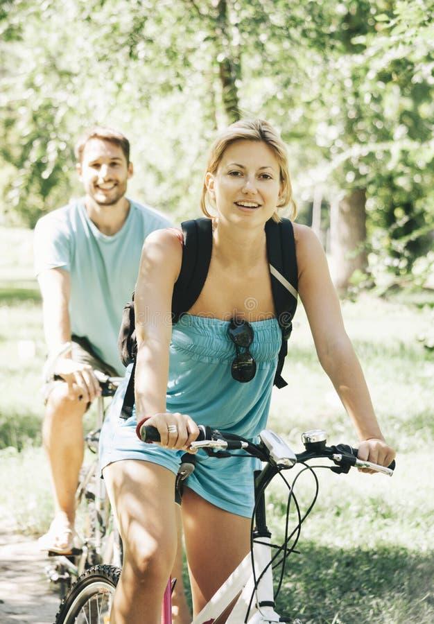 Bicicleta feliz da equitação dos pares imagem de stock