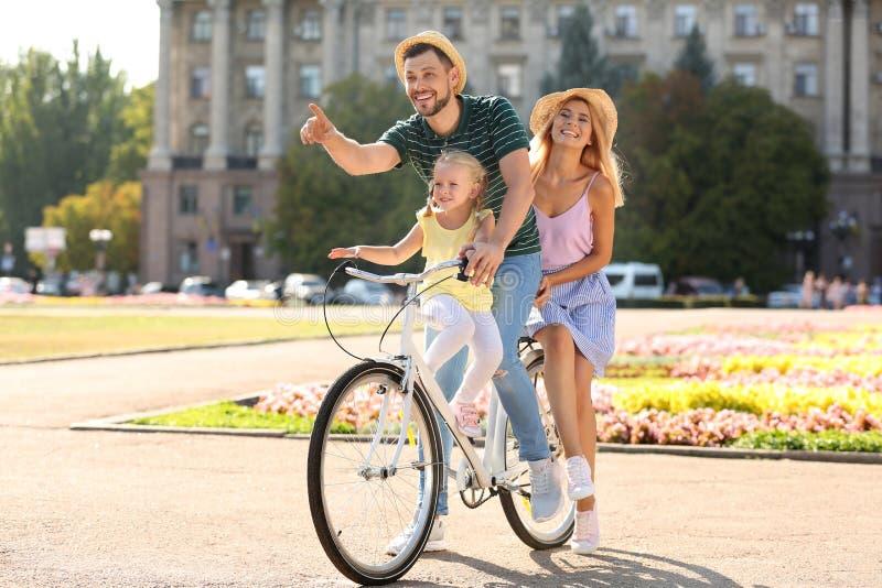 Bicicleta feliz del montar a caballo de la familia al aire libre imagen de archivo
