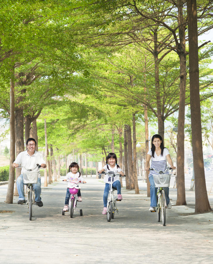 Bicicleta feliz del montar a caballo de la familia fotografía de archivo