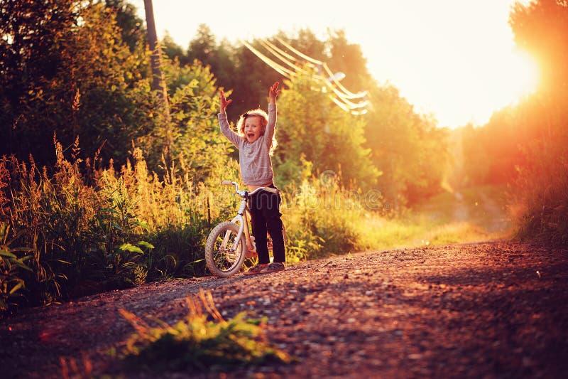 Bicicleta feliz del montar a caballo de la muchacha del niño en puesta del sol del verano en la carretera nacional imagenes de archivo