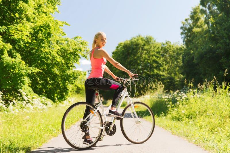 Bicicleta feliz del montar a caballo de la mujer joven al aire libre fotografía de archivo