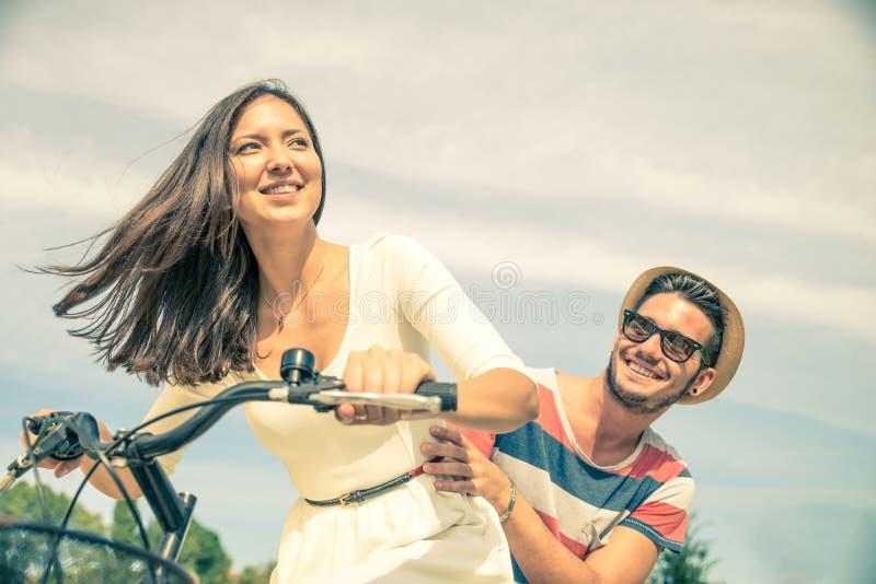 Bicicleta feliz del montar a caballo de los pares al aire libre foto de archivo libre de regalías