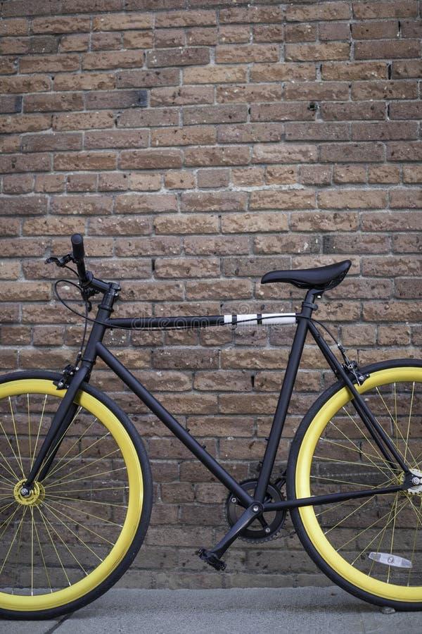 Bicicleta inclinada contra la pared de ladrillo imagenes de archivo