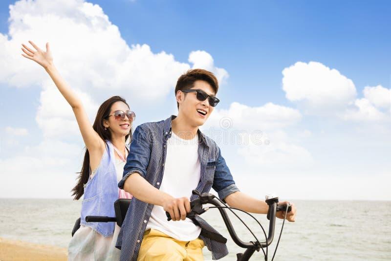 Bicicleta joven del montar a caballo de los pares en la playa fotos de archivo