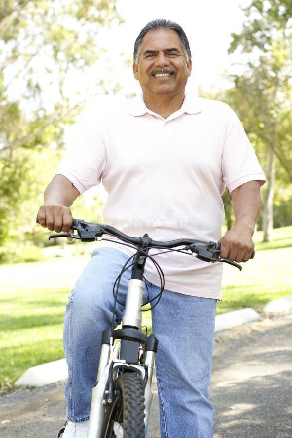 Bicicleta latino-americano sênior da equitação do homem no parque imagens de stock royalty free