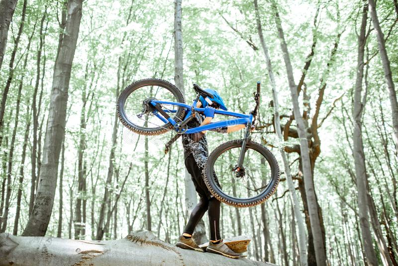 Bicicleta levando do ciclista ao montar extremamente na floresta foto de stock royalty free