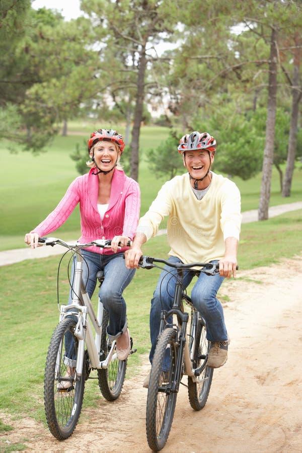 Bicicleta mayor del montar a caballo de los pares en parque fotos de archivo libres de regalías