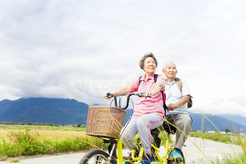 Bicicleta mayor feliz del montar a caballo de los pares en la carretera nacional foto de archivo