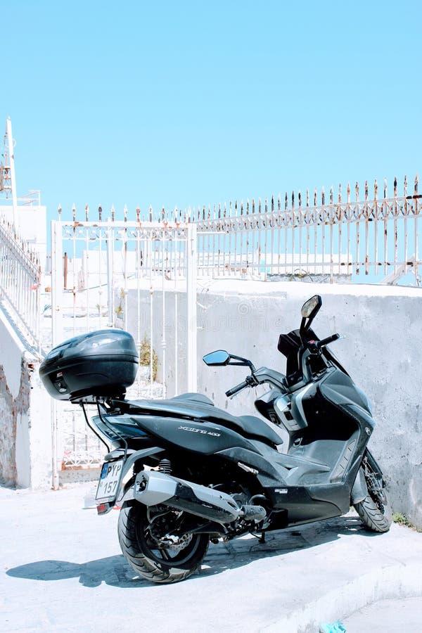 Bicicleta motorizada do preto estacionada por uma parede da praia imagens de stock