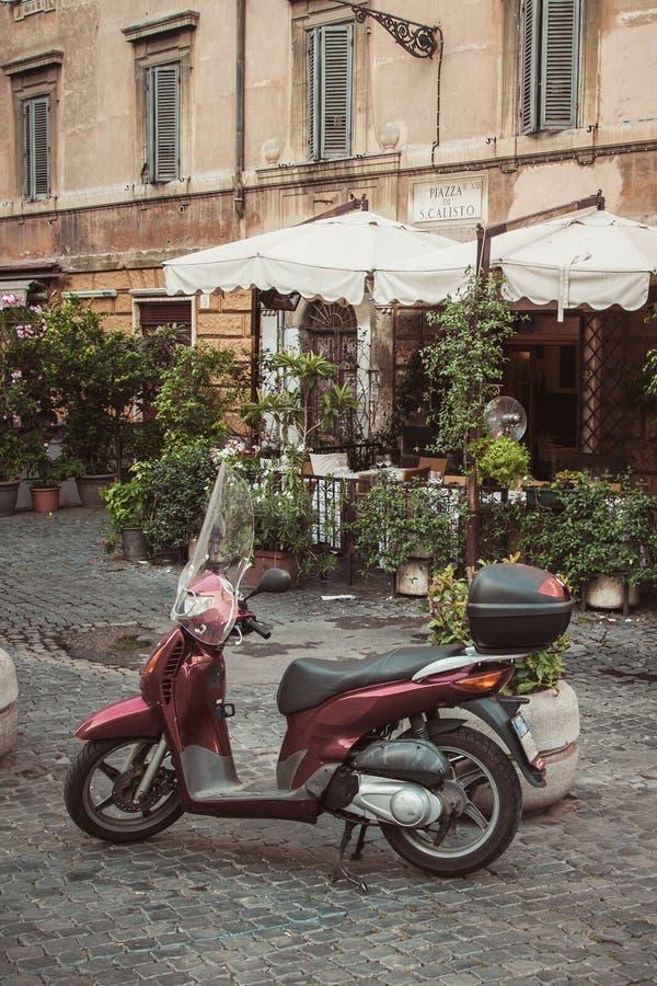 A bicicleta motorizada estacionou na rua na frente do café em Trastevere, Roma, Itália fotografia de stock