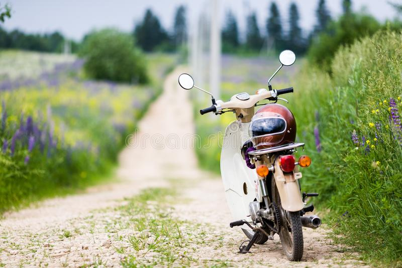 Bicicleta motorizada retro do luz-motor velho clássico com um capacete da velha escola imagens de stock
