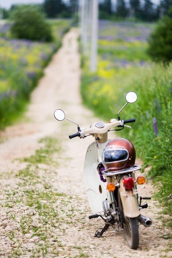Bicicleta motorizada retro do luz-motor velho clássico com um capacete da velha escola fotos de stock royalty free