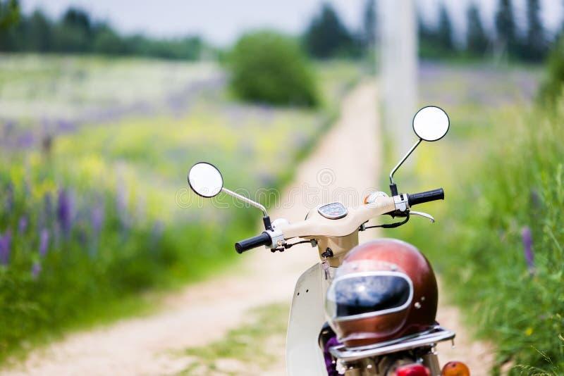 Bicicleta motorizada retro do motor leve velho clássico com um capacete da velha escola sobre imagens de stock royalty free