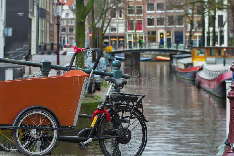 Bicicleta o bakfiets holandeses en el canal de la calle de Amsterdam con el fondo del puente imagen de archivo