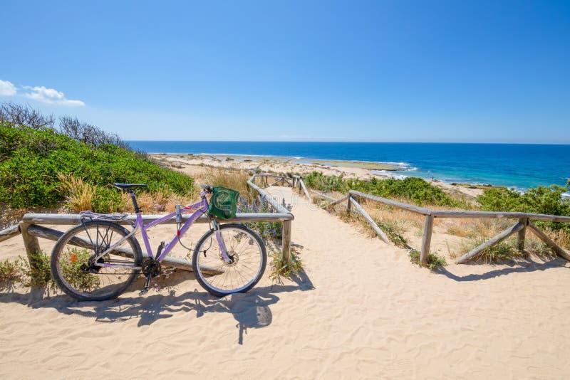 Bicicleta púrpura parqueada al lado del acceso de la playa en calzada de la arena abajo a la costa del océano en el cabo Trafalga fotos de archivo