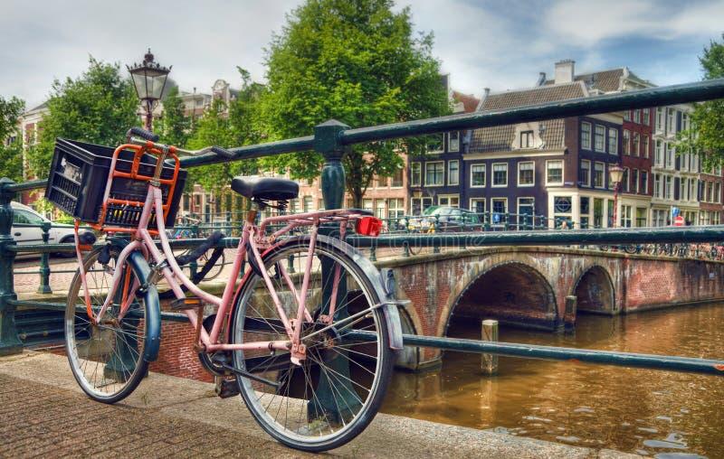 Bicicleta parqueada rosa al lado de un canal en Amsterdam imagenes de archivo