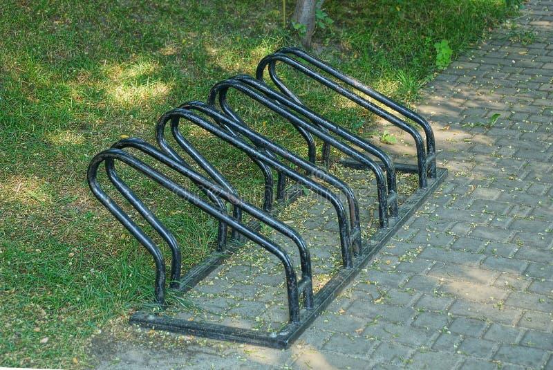 Bicicleta preta do ferro que estaciona no passeio da grama verde foto de stock royalty free