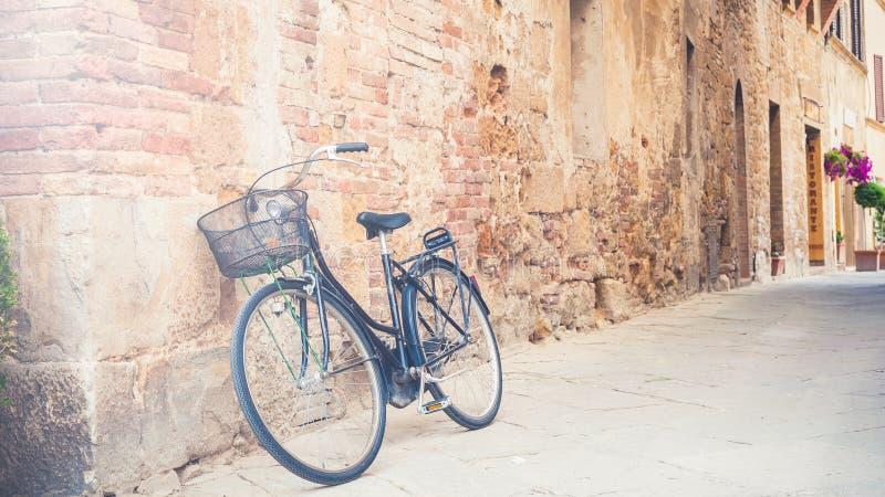 A bicicleta preta do vintage saiu em uma rua em Toscânia, Itália fotografia de stock royalty free