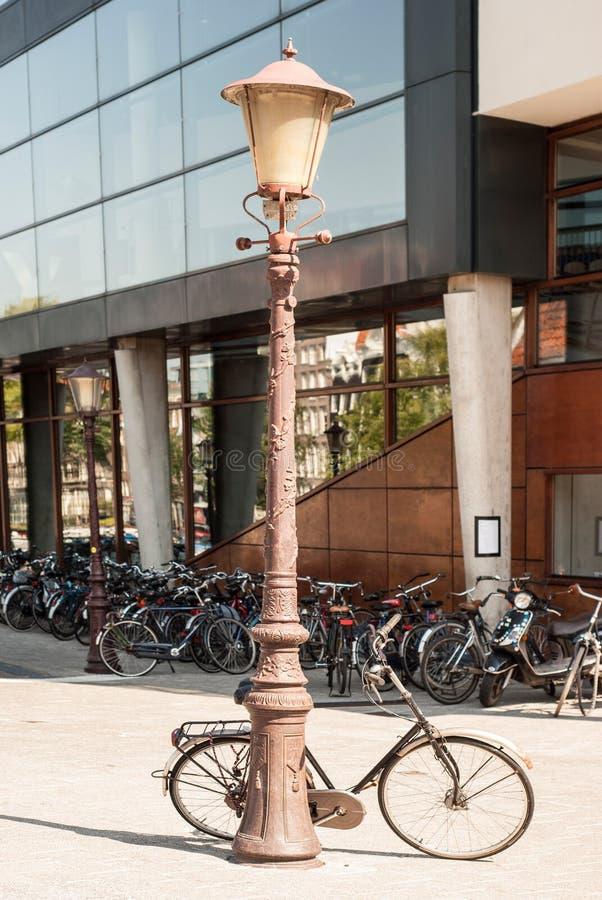 Bicicleta que se inclina contra una lámpara de calle fotografía de archivo libre de regalías
