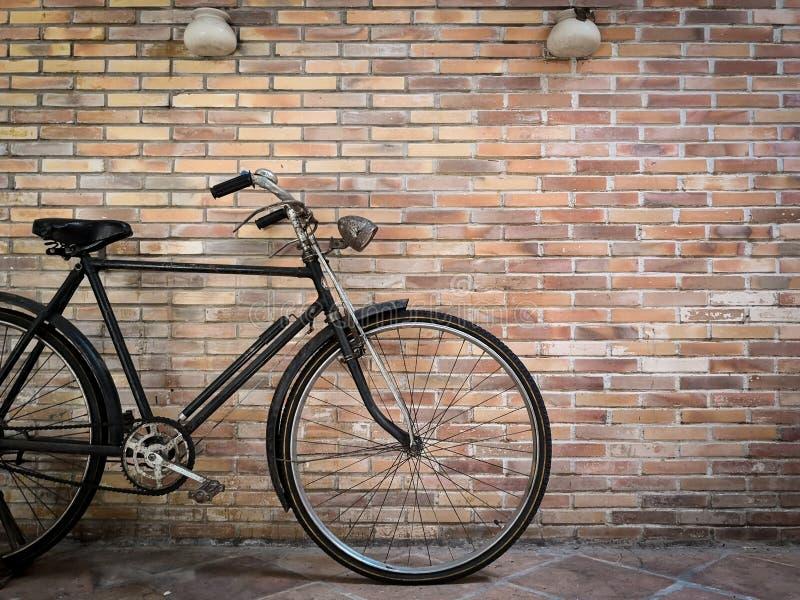 Bicicleta retra delante de la pared de ladrillo vieja foto de archivo