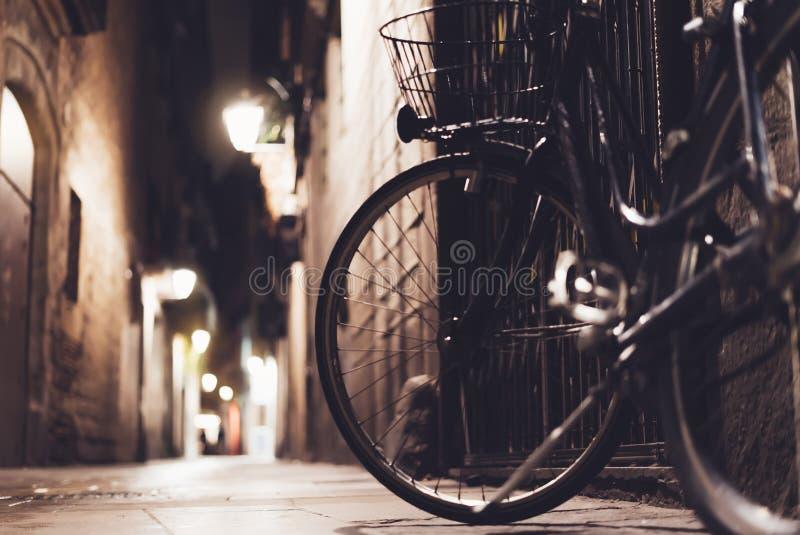 Bicicleta retra en la ciudad vieja de la noche en la llamarada en arquitectura de la noche, bici de la luz del bokeh del fondo de foto de archivo