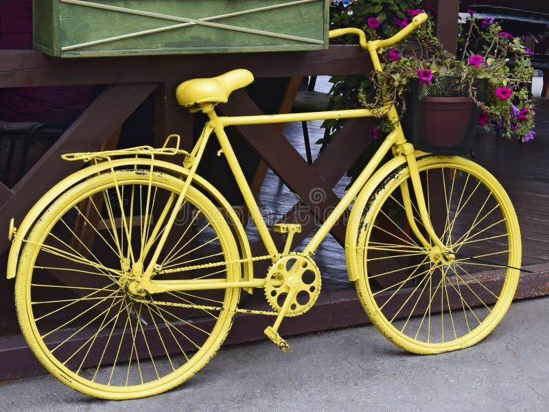Bicicleta retro amarela com uma cesta das flores foto de stock